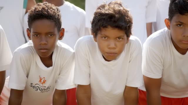vídeos de stock, filmes e b-roll de brazilian youth soccer team stare down camera with intensity at game time - esporte de competição