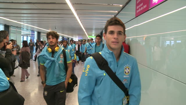 brazil's soccer squad arrives at heathrow for 2012 london olympics / long walking shot of oscar followed by brief shots of other team members... - internationaler fußball stock-videos und b-roll-filmmaterial
