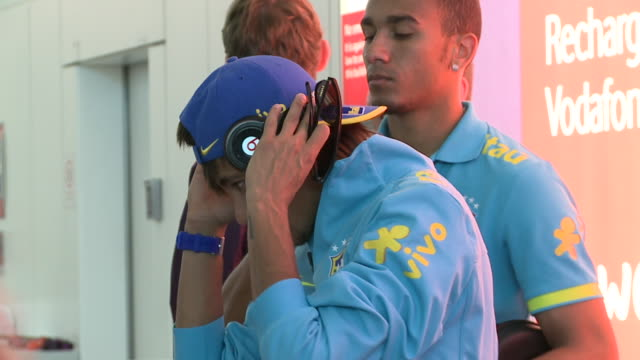 brazil's soccer squad arrives at heathrow for 2012 london olympics / naymar stands and waits headphones on head and cap reversed although looks away... - neymar da silva stock-videos und b-roll-filmmaterial