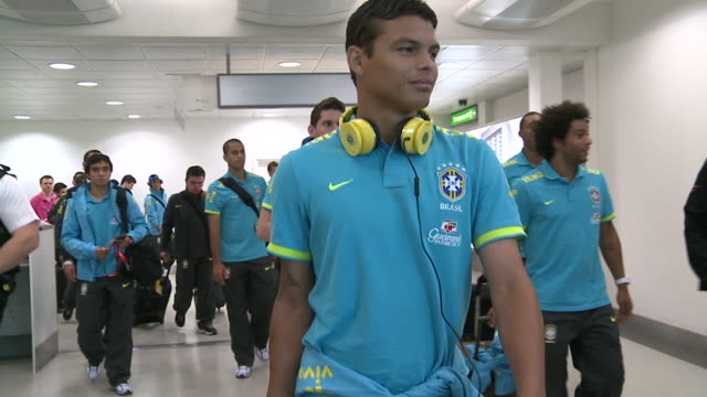 brazil's soccer squad arrives at heathrow for 2012 london olympics / long walking shot of group / long close up of thiago silva then others including... - neymar da silva stock videos & royalty-free footage