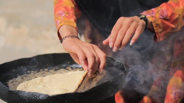 Bread and tea being made outdoors by mother and daughter in Raymah a remote mountain village in Yemen