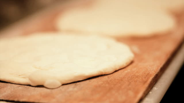 Bread dough is picked up with a wooden paddle.
