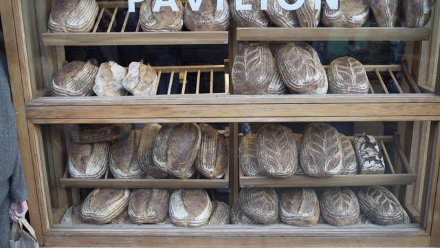 vídeos de stock e filmes b-roll de bread in a bakery window. - padaria