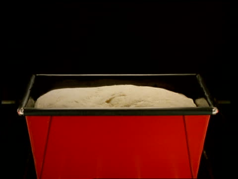 t/l - cu bread in red bread tin, rising in oven, black background - bread stock videos & royalty-free footage