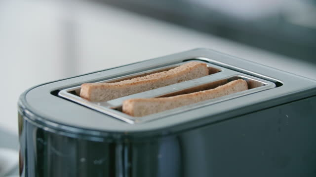 bread is toasted as toast in a toaster for breakfast. - toaster appliance stock videos & royalty-free footage