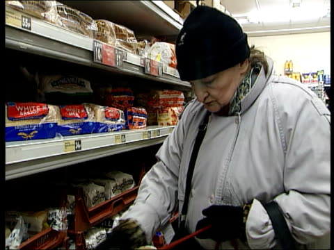Bread price wars in supermarkets ENGLAND Loaf of Asda white bread Shop assistant filling shelves with bread Bread on shelves CS Bread price '9p'...