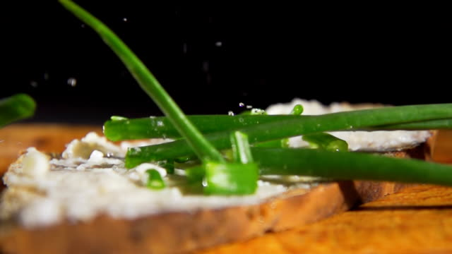 hd slow motion: bread, spread and spring onion - peasant bread stock videos and b-roll footage
