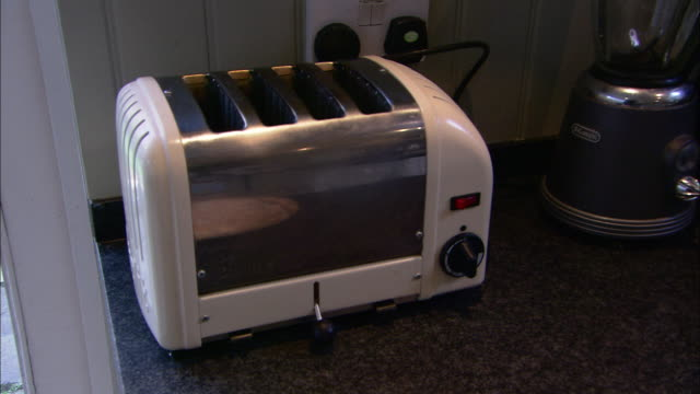 a bread toaster is plugged into a wall outlet. - toaster appliance stock videos & royalty-free footage