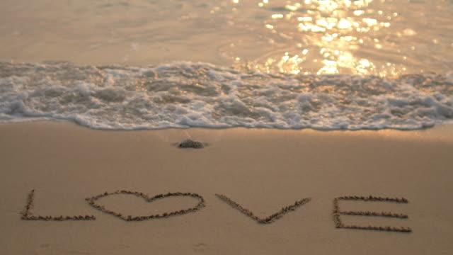 Kurzurlaub in meinem Herzen und Gebrochenes Herz Konzept (Welle des Meeres löschen Liebe -Schriftzug am Strand ein Sonnenuntergang Zeit