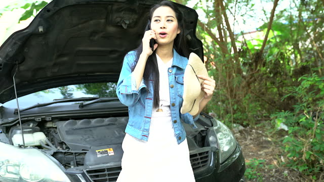 breakdown of the car on the road. the girl is waiting for the tow truck. the girl is upset by the car breakdown. - tow truck driver stock videos and b-roll footage