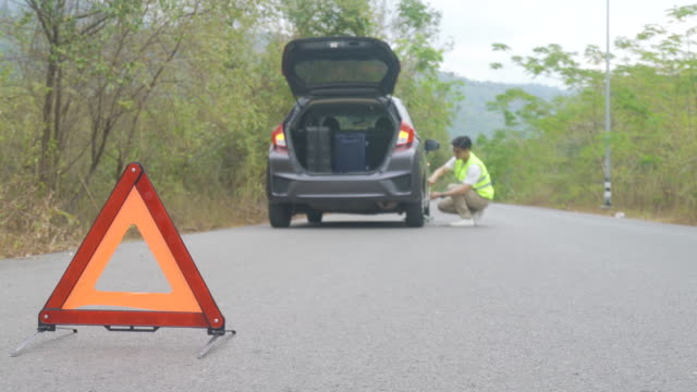 breakdown triangle sign on road with worried asian man repairing and change tire while waiting insurance or car service center company come after car breakdown on country road in background. - triangle shape stock videos & royalty-free footage