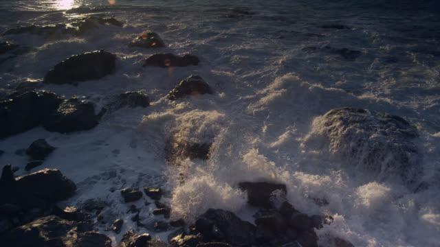 Breaker wave crashes onto rocky coast at sunset, New Zealand