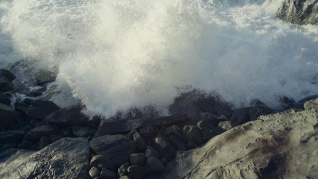 Breaker wave crashes onto rocky coast, New Zealand