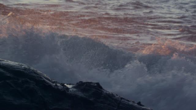 Breaker wave rolls onto rocky coast at sunset, New Zealand