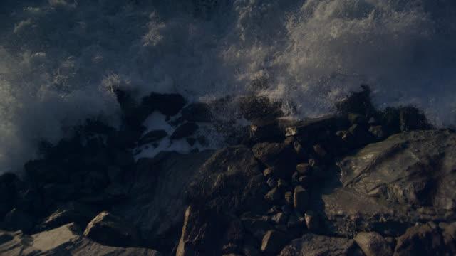 Breaker waves roll onto rocky coast at sunset, New Zealand