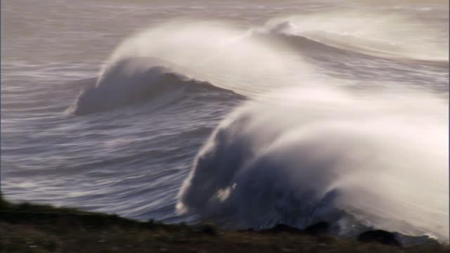 Breakers roll onto rocky coast at sunrise, Easter Island