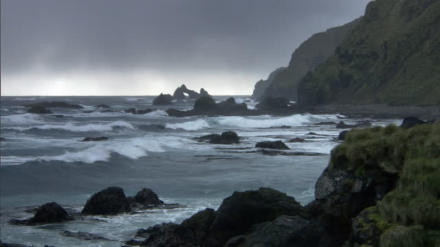 breakers roll onto rocky coast, macquerie island, australia - klippe stock-videos und b-roll-filmmaterial