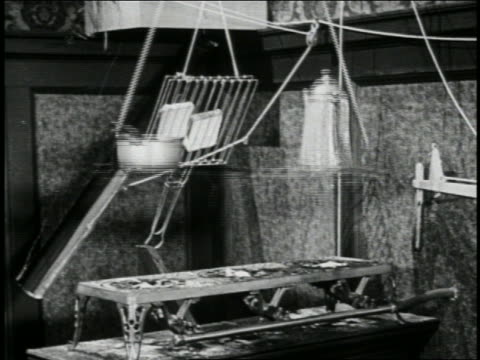 b/w 1923 breakfast cookware on strings lowering over gas stove / short - 1923 stock-videos und b-roll-filmmaterial