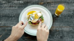 Breakfast - fried egg with bacon and cheese, top view in cafe with hands and fork