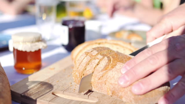 Breakfast in sun cutting bread close-up
