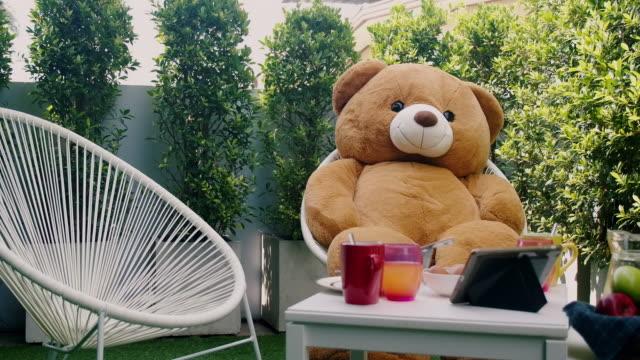 stockvideo's en b-roll-footage met ontbijt dat in huis openluchttuin, met teddybeerzitting in stoel wordt geplaatst. - teddybeer