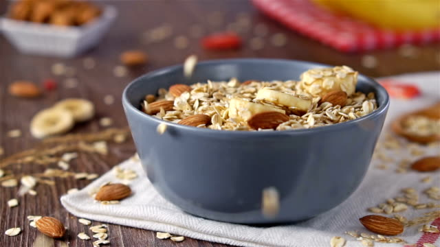 Breakfast smoothie bowl with banana, granola and Almond. Slow Motion