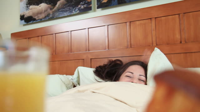 cu pov breakfast tray, orange juice and muffin being brought to woman in bed, hoboken, new jersey, usa - prima colazione video stock e b–roll