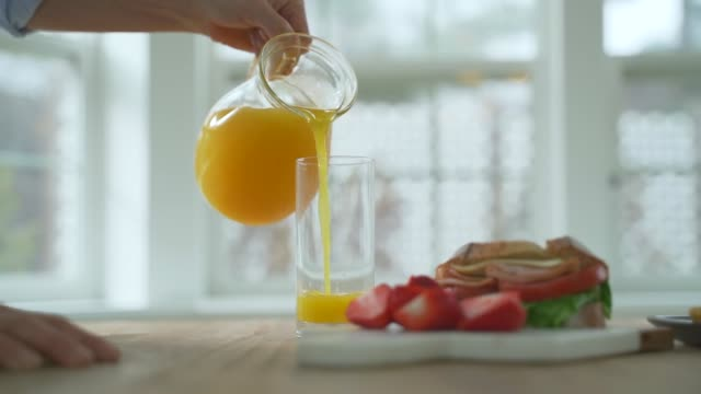 breakfast with a glass of juice and strawberry - orangensaft stock-videos und b-roll-filmmaterial