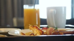 Breakfast with fried bacon and orange juice