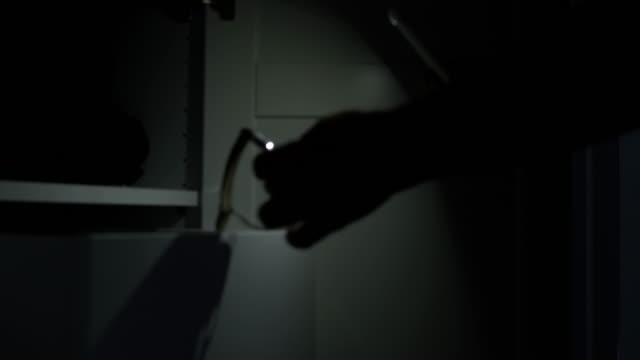 vídeos de stock, filmes e b-roll de arrombando e entrando. assaltante masculino entrando em uma sala escura. - lanterna elétrica
