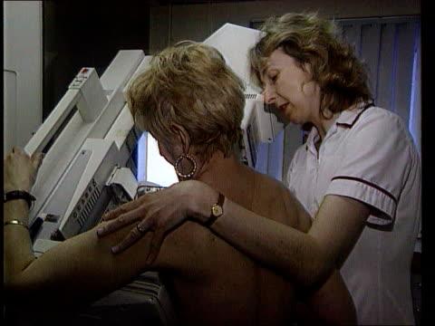 vídeos y material grabado en eventos de stock de breast cancer-gene link: register; lib nurse assists woman to have mammogram - eslabón