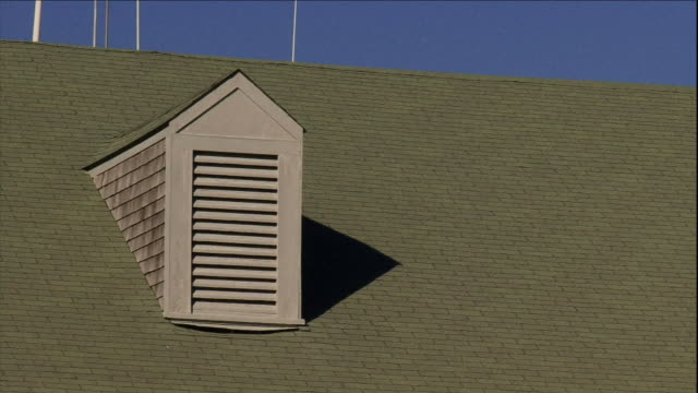 a breeze blows poles on top of a green roof with a dormer. - air duct stock videos & royalty-free footage