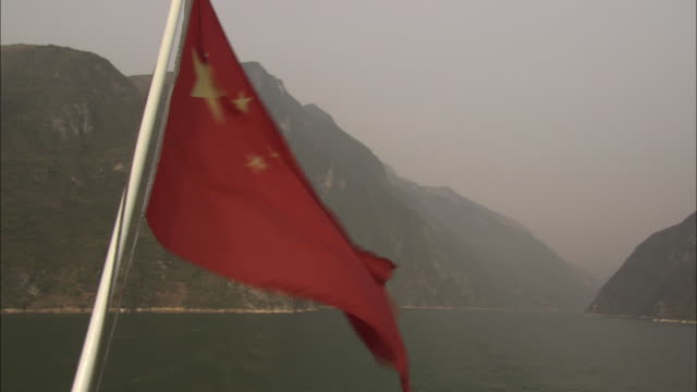 a breeze rustles the chinese flag on a pole. - air pollution stock videos & royalty-free footage