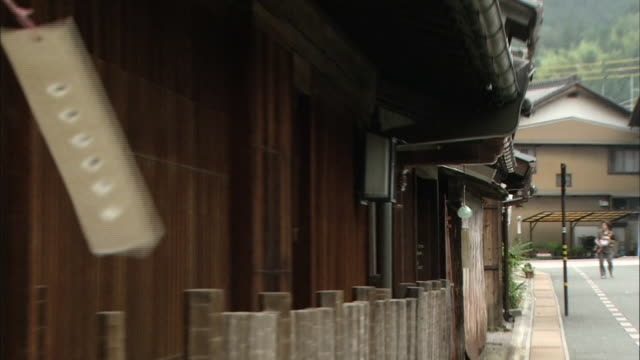 a breeze rustles wind-bells hanging from eaves as traffic travels past a row of old houses in mino, japan. - eaves stock videos and b-roll footage