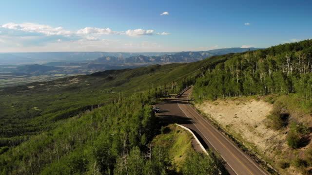 breezy sunny summer day aerial 4k video von grand mesa national forest highway 65 - kiefernwäldchen stock-videos und b-roll-filmmaterial