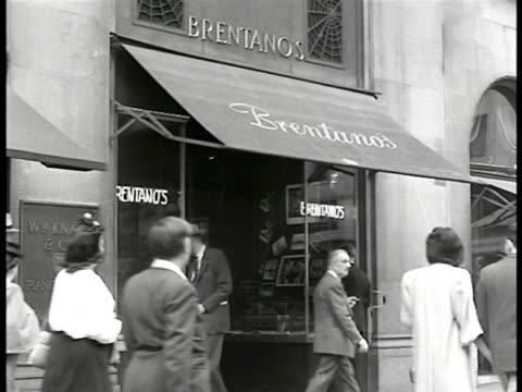 ws 'brentanos' book shop new yorkers int woman looking at books on table display sign 'by authors of the new france' cu books 'aurelien aragonpoet of... - 1946年点の映像素材/bロール