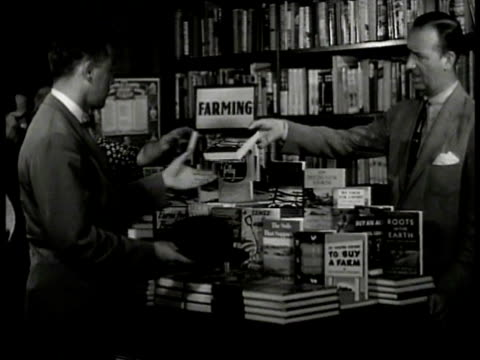vídeos de stock, filmes e b-roll de brentano's bookstore int bookstore in farming section salesman handing book to man in suit farming book display cu male hands opening book to cover... - livraria