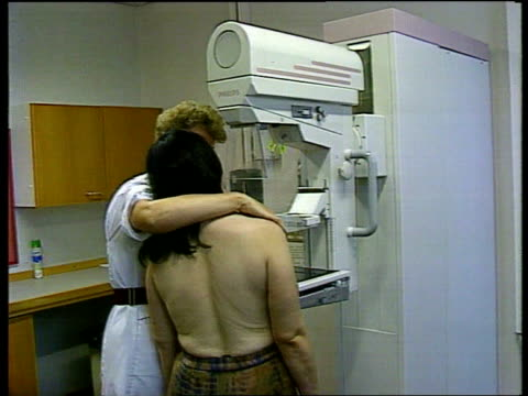 Int BV Nurse giving woman breast scan on machine Nurse along to machine Nurse pressing button for scan XRay of breast