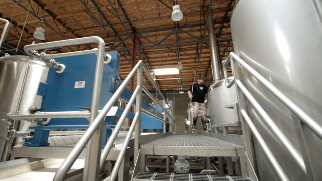 ts ws brew master at micro brewery walks up to mash tank and stirs mash with large mash paddle / thousand palms, california, usa - 醸造所点の映像素材/bロール