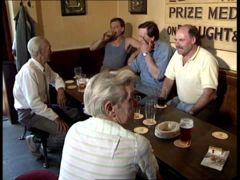 vidéos et rushes de 17 int the tom hoskins pub 2422 two people at bar chatting to barmaid pints pulled customers in pub drinking more pints of hoskins pulled london ec1... - plaque rue