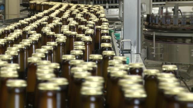 cu brewery bottling plant on conveyer belt in warsteiner ag / warstein, north rhine westphalia, germany - 豊富点の映像素材/bロール