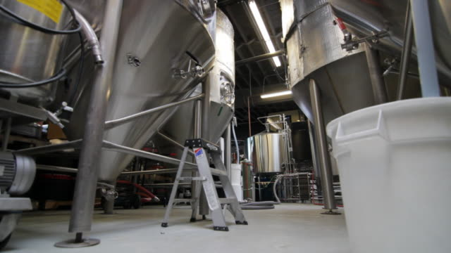brewery with metal tanks and worker. - ステンレス点の映像素材/bロール