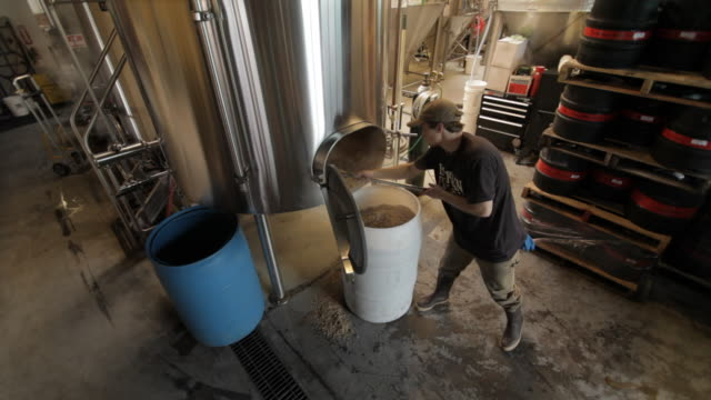 brewery worker shovels grains into large bucket - brauerei stock-videos und b-roll-filmmaterial
