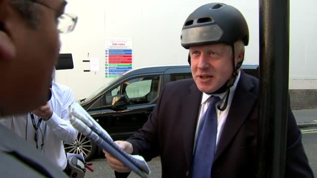 boris johnson uses newspaper column to attack theresa may's brexit strategy england london soho ext boris johnson mp interview while unlocking bike... - boris johnson stock-videos und b-roll-filmmaterial