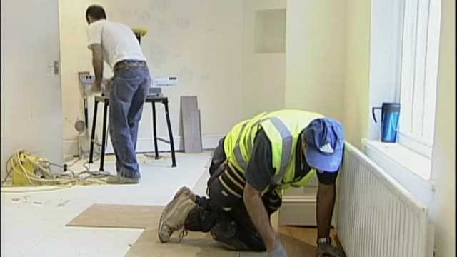 Businesses alarmed by EU immigration proposals T24100607 / TX London Builder laying floorboards as renovate room Bulgarian plumber along