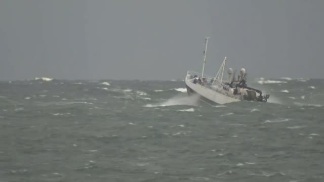 stockvideo's en b-roll-footage met leaders agree talks can move on to phase two; t07021725 / tx 7.2.2017 at sea: ext fishing boat along in harbour long shot of fishing boat riding... - gulf coast states