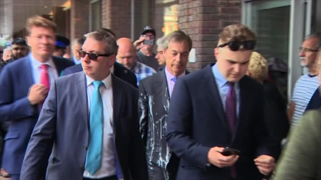 vidéos et rushes de nigel farage hit with milkshake england newcastle ext paul crowther led away by police officer / various of nigel farage mep along with others /... - milk shake