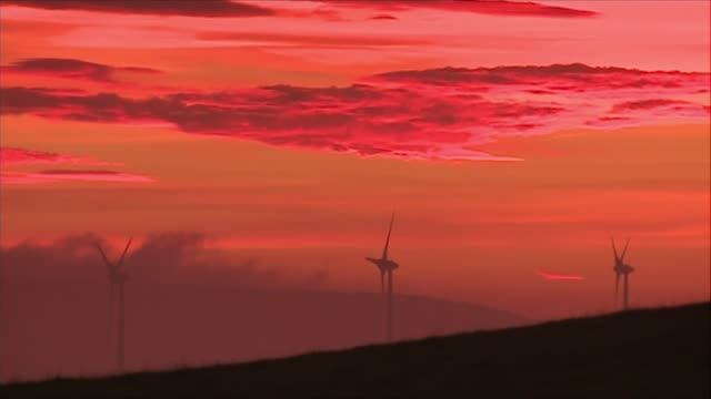 Nicola Sturgeon outlines cost to Scottish economy of leaving EU without trade agreement DATE Wind turbines with red sky behind