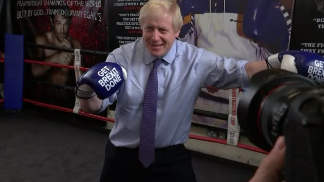 opinion on uk's post brexit trade policy england manchester wythenshawe int boris johnson photocall wearing boxing gloves reading 'get brexit done' - boxhandschuh stock-videos und b-roll-filmmaterial
