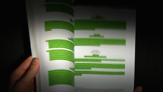 UK and EU agree Brexit transition deal ENGLAND INT Various of hand flicking through EU's draft treaty for Brexit document with green highlighted...